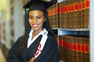 beautiful african female graduate in library on graduation day