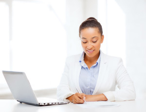 business and technology concept - african businesswoman with lap