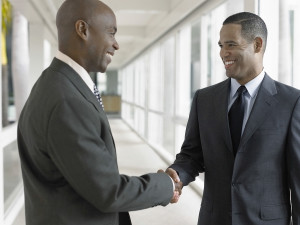 Happy African American businessmen shaking hands while standing