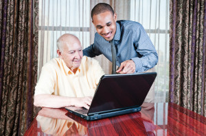 Young Man And Senior Male Working On Computer